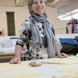 Senior clothing designer and artist poses at her work space in fiber arts studio